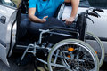 Disabled driver consisting his wheelchair handicapped sitting already in car and Stock Image