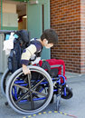 Disabled kindergartner in wheelchair on playground at recess trying to manuever Royalty Free Stock Photography