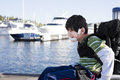 Disabled little boy in wheelchair out on pier by lake biracial six year old pushing himself Royalty Free Stock Image