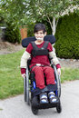 Disabled little boy in wheelchair outdoors biracial six year old sitting on sidewalk Royalty Free Stock Photo