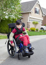 Disabled little boy in wheelchair outdoors biracial six year old sitting on sidewalk Stock Image