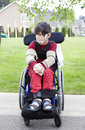 Disabled little boy in wheelchair outdoors biracial six year old sitting on sidewalk Royalty Free Stock Photos