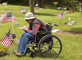Disabled man at the cemetery in a wheelchair visits a fallen brother Royalty Free Stock Photos
