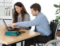 Disabled man in the office wheelchair and his associate on workplace Royalty Free Stock Image