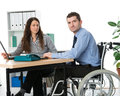 Disabled man in the office wheelchair and his associate on workplace Stock Photos
