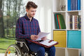 Disabled man viewing documents on a wheelchair Stock Images