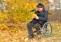 Disabled man in a wheelchair collecting leaves senior gentleman sitting holding his crutches vivid yellow fall or autumn the park Stock Photos
