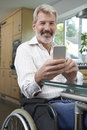 Disabled Man In Wheelchair Texting On Mobile Phone At Home Royalty Free Stock Photo