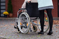 Disabled with nurse walking elder person on wheelchair Royalty Free Stock Images