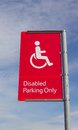 Disabled parking sign a red and white in the car park of a supermarket copyspace in sky Stock Images