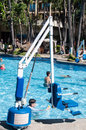 Disabled person pool lift ada standard used at swimming pools in order to lower a into the water this device is located at Royalty Free Stock Photo