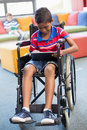 Disabled schoolboy on wheelchair using digital tablet in library Royalty Free Stock Photo