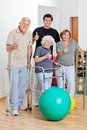 Disabled senior people with trainer showing thumbs portrait of up sign Stock Photography