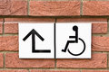 Disabled sign for wheelchair access on a brick wall Stock Photos