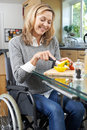 Disabled Woman In Wheelchair Preparing Meal In Kitchen Royalty Free Stock Photo