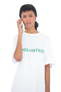 Disappointed black haired volunteer calling someone with her mobile phone on white background Stock Photos