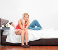 Disappointed female sitting on a bed Royalty Free Stock Photos