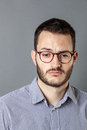 Disappointed man expressing emptiness and disillusion feeling depressed portrait of a young with beard eyeglasses grey Stock Photography