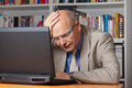 Disappointed man with laptop elderly businessman stunned and stressed in front of his Royalty Free Stock Image
