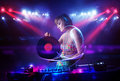 Disc jockey girl playing music with light beam effects on stage pretty young Stock Image