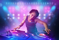 disc jockey mixing music on turntables on stage with lights and stroboscopes Royalty Free Stock Photo