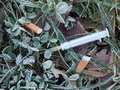 Discarded syringe in gutter Royalty Free Stock Photo