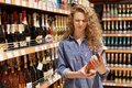 Discontent curly young woman in denim clothes looks with unhappy expression at bottle of wine, reads information abut products, ne Royalty Free Stock Photo