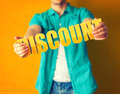 Discount man holds word on bright colorful background Royalty Free Stock Photos