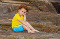 Discouraged boy sitting on rocks Royalty Free Stock Photography