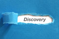 Discovery appearing behind blue color paper Stock Photo