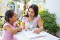 Discussing a book little girl and her mother drinking milkshakes and Royalty Free Stock Photos