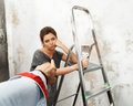 Disgruntled woman with ladder and brush man s hand pouting on a worker Stock Photo