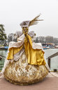 Disguised person annecy france march image of an unidentified in big golden costume posing near the lake during the annecy Royalty Free Stock Photos