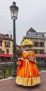 Disguised person annecy france march image of an unidentified in an orange costume posing near a canal during the annecy venetian Royalty Free Stock Images