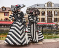 Disguised persons annecy france march two in fancy costumes poses in near a water canal during the annecy venetian carnival yearly Stock Photos