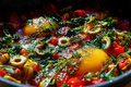 Dish egg in a frying pan with olives, pepper and greens Royalty Free Stock Photo