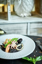 Dish of risotto with squid ink on grey plate jpg