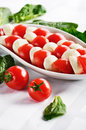 Dish with sliced mozzarella cheese balls and ripe cherry tomatoe Royalty Free Stock Photo