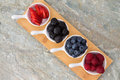 Dishes of fresh berries arranged diagonally on a small wooden board on a stone kitchen counter with copyspace ready for tasting Royalty Free Stock Photography
