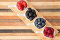 Dishes of fresh berries on decorative striped wood arranged in a diagonal row a small wooden board including blackberries Royalty Free Stock Images