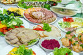 Dishes on white plates laid table with many Royalty Free Stock Images
