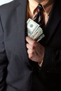 Dishonest businessman close up of a business mans hand hiding money in his suit jacket pocket Royalty Free Stock Photos