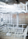 Dishwasher empty close up rady to fill with steam inside Royalty Free Stock Image