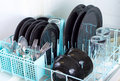 Dishwasher rack loaded with clean plates glasses and silverware Royalty Free Stock Images