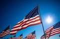 A dispaly of american flags with a sky background many blue Stock Photos