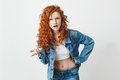 Displeased brutal redhead girl looking at camera not understanding over white background. Copy space. Royalty Free Stock Photo