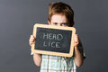 Displeased child hiding behind a school slate scaring head lice Royalty Free Stock Photo