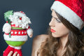 Displeased frown dressed in red hat looking at santa claus woman gift toy it may not be desired gift for an adult woman on Royalty Free Stock Photo