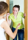 Displeased girl visiting neighbour sad adult at the door Royalty Free Stock Images