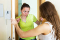 Displeased girl visiting neighbour sad at the door Royalty Free Stock Images